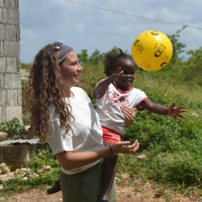 A volunteer working with children in Jamaica does an activity with a ball to improve hand-eye coordination at our Childcare Project.